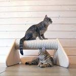 Два кота около напольной когтеточки в форме бревна