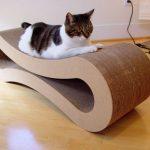 кошка лежит на горизонтальной когтеточке в форме восьмёрки
