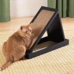 рыжий кот царапает наклонную когтетку в виде коврика на подставке
