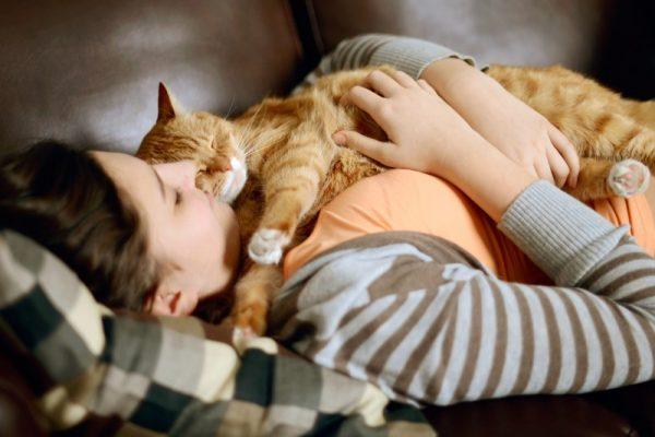Кот лежит на груди девушки, а она его обнимает