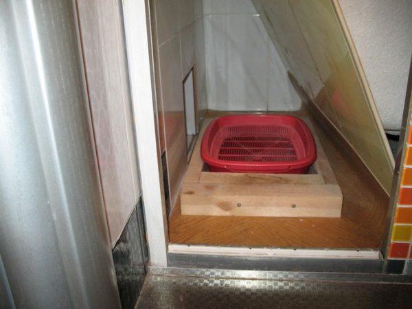 Красный кошачий лоток стоит в месте, отгороженном дощечкой