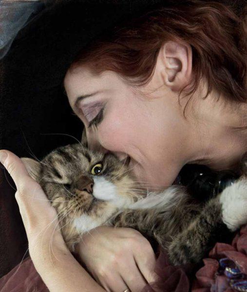Женщина в шляпе целует кота