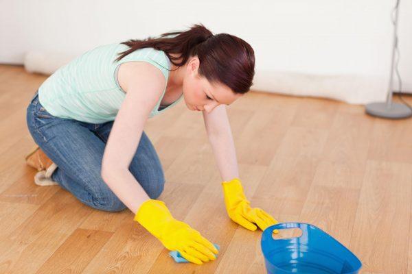 девушка в жёлтых перчатках моет напольное покрытие