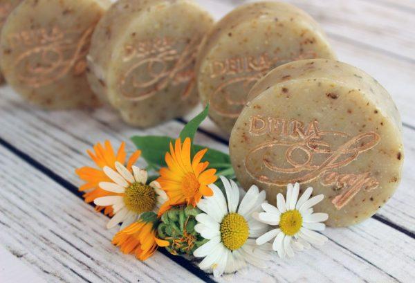 цветки ромашки, календулы и коричневое мыло
