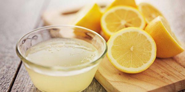 половинки лимона на разделочной доске и лимонный настой в миске