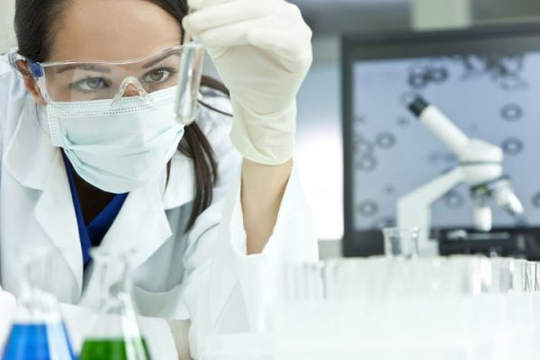 Лаборант в белом халате с пробиркой в руках