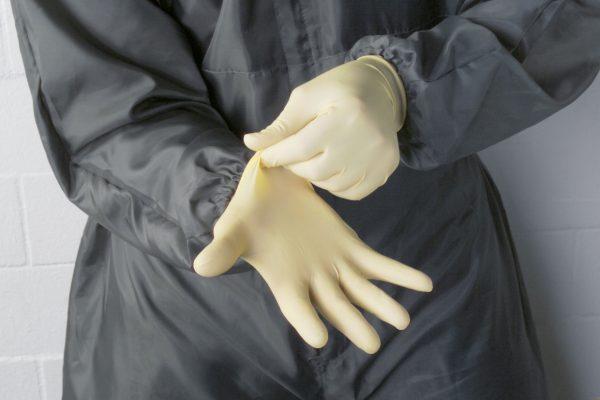 Человек в резиновых перчатках и ОЗК